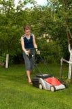De jonge vrouw maait gras Royalty-vrije Stock Foto