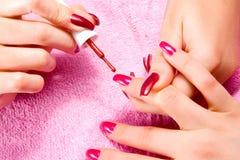 De jonge vrouw maakt de manicure Royalty-vrije Stock Afbeelding