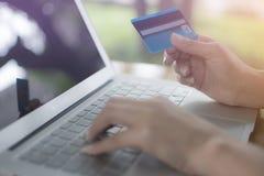 De jonge vrouw maakt een aankoop op Internet langs van laptop online stock foto