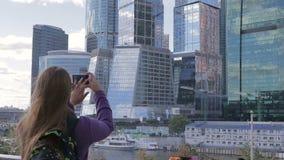 De jonge vrouw maakt een foto van hoge wolkenkrabber gebruikend de telefooncamera van de smartphone mobiele cel stock videobeelden
