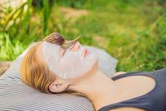 De jonge vrouw maakt een gezichtsmasker met slakslijm Slak die op een gezichtsmasker kruipen royalty-vrije stock foto