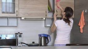 De jonge vrouw maakt de flat schoon, die de kasten in de keuken wrijven stock footage