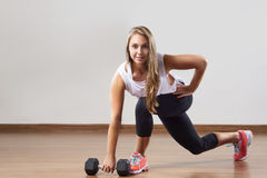 De jonge vrouw maakt oefeningen met gewicht in gymnastiek Stock Foto's