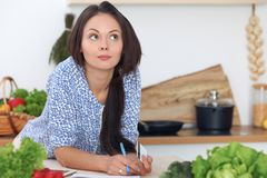 De jonge vrouw maakt online het winkelen door tabletcomputer en creditcard Huisvrouw gevonden nieuw recept voor binnen het koken Stock Foto