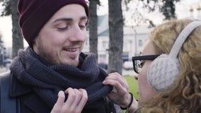 De jonge vrouw maakt sjaal aan haar vriend recht stock video