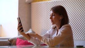 De jonge vrouw maakt vidiovraag gebruikend smartphone en oortelefoons stock video