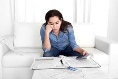 De jonge vrouw maakte zich thuis in de bankdocumenten van de spanningsboekhouding ongerust met calculator Stock Foto's