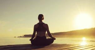 De jonge vrouw mediteert in Lotus Pose-zitting op pijler dichtbij het overzees bij zonsondergang stock footage