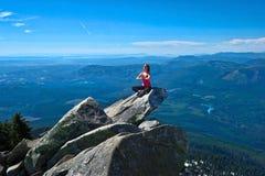 De jonge vrouw mediteert op rots boven mooie vallei royalty-vrije stock foto's