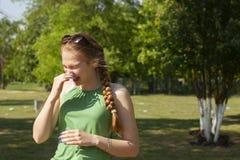De jonge vrouw met allergie tijdens zonnige dag veegt haar neus af royalty-vrije stock foto's