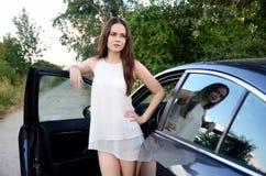 De jonge vrouw met auto parkeerde bij de landweg Stock Afbeelding