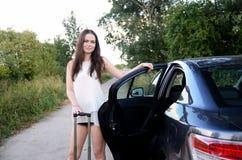 De jonge vrouw met auto parkeerde bij de landweg Royalty-vrije Stock Afbeelding