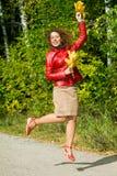 De jonge vrouw met bladeren dient binnen sprong in de herfst in Stock Afbeeldingen