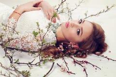 De jonge vrouw met blond krullend haar draagt elegant kantkleding en juweel Stock Foto