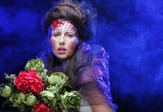 de jonge vrouw met creatief maakt omhoog het houden van bloemen Stock Foto's