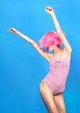 De jonge vrouw met creatief pop-art maakt omhooggaande en roze pruik bekijkend de camera op blauwe achtergrond royalty-vrije stock fotografie