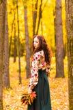De jonge vrouw met de herfst gaat ter beschikking weg Stock Foto's