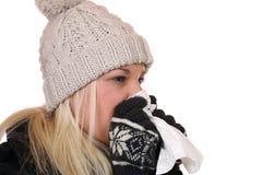 De jonge vrouw met een koude en griepvirus die in een weefsel niezen is Stock Foto's