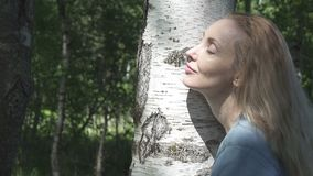 De jonge vrouw met een lang eerlijk haar omhelst en strijkt een witte boomstam van een berk in de zomer zonnige dag stock video