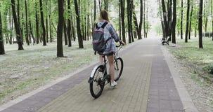 De jonge vrouw met een rugzak cirkelt in het park stock videobeelden