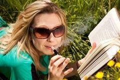 De jonge vrouw met elektrische sigaret las boek Royalty-vrije Stock Foto's