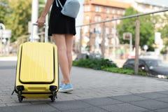 De jonge vrouw met geel draagt koffer Royalty-vrije Stock Foto's