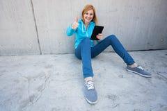 De jonge vrouw met het digitale tablet tonen beduimelt omhoog Royalty-vrije Stock Foto's