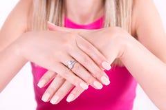 De jonge vrouw met het naakte gel van het de spijkerspoetsmiddel van de kleurenmanicure en de diamanten bellen op vinger royalty-vrije stock foto
