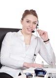 De jonge vrouw met hoofdtelefoon zit bij het bureau royalty-vrije stock fotografie