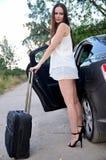 De jonge vrouw met kleine bagage bevindt zich dichtbij auto Stock Afbeelding