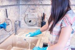 De jonge vrouw met lang donker haar maakt een granietgootsteen in de keuken schoon royalty-vrije stock foto