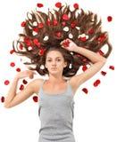 De jonge vrouw met lang haar en nam bloemblaadjes toe Stock Foto