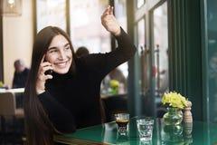 De jonge vrouw met lang haar geeft hallo-vijf aan iemand, drinkt koffie die rust in koffie hebben dichtbij windowing royalty-vrije stock foto