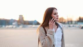 De jonge vrouw met lang haar loopt langs de straat en spreekt op de telefoon stock videobeelden