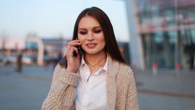 De jonge vrouw met lang haar loopt langs de straat en spreekt op de telefoon stock video