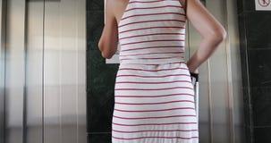 De jonge vrouw met lang haar wacht op de lift in het hotel stock videobeelden