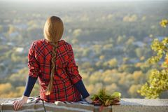 De jonge vrouw met lang haar zit op een heuvel overziend de stad royalty-vrije stock foto's