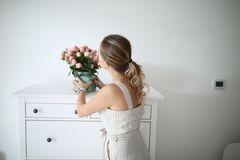 De jonge vrouw met lang krullend haar zet de vaas op de ladenkast in de woonkamer stock fotografie