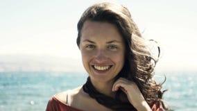 De jonge vrouw met mooie glimlach en het haar die zich in wind tegen overzees landschap bevinden en bekijken camera stock video
