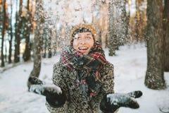 De jonge vrouw met sneeuw dient binnen de winterbos in Stock Foto's