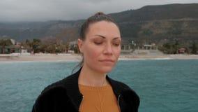 De jonge vrouw met sproeten kijkt rond de kust in bewolkt weer stock videobeelden