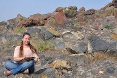De jonge vrouw met tabletcomputer in handen zit op stenen Stock Foto