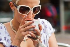 De jonge vrouw met tatoegeringen drinkt koffie Royalty-vrije Stock Afbeeldingen