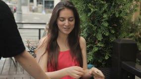 De jonge vrouw met telefoon zit in openlucht in de zomerkoffie stock footage