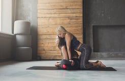 De jonge vrouw met yogainstructeur in geschiktheidsclub, lotusbloem stelt royalty-vrije stock afbeelding