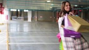 De jonge vrouw met zakken verheugt zich na het winkelen donkerbruine vrouw met multi-colored pakketten naast de opslag verkoop bi stock video
