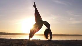 De jonge vrouw in mooie gekleurde die yogabroek doet yogaoefening Urdhva Dhanurasana ook als stijgende booghouding wordt bekend stock footage