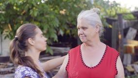 De jonge vrouw nadert omhelzingen en kust haar hogere moeder stock video