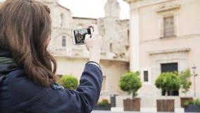 De jonge vrouw neemt beelden van een gebouw in Valencia met haar telefoon stock footage