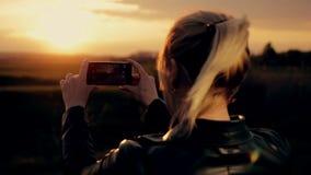 De jonge vrouw neemt de zon aan uw smartphone stock video